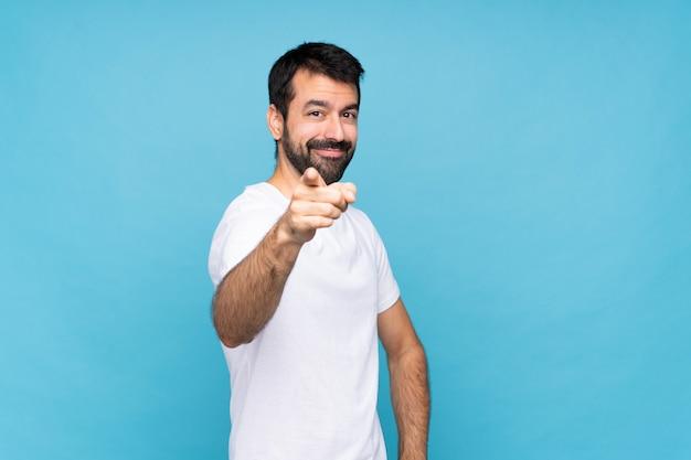 Jovem com barba sobre o dedo isolado de pontos azuis para você com uma expressão confiante