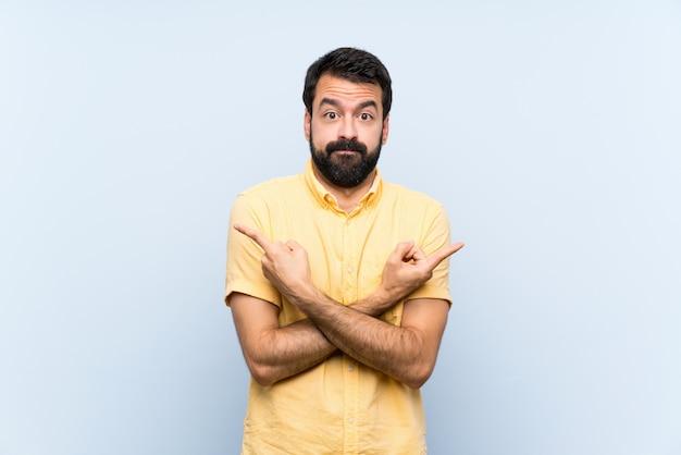 Jovem com barba sobre parede azul isolada, apontando para as laterais tendo dúvidas