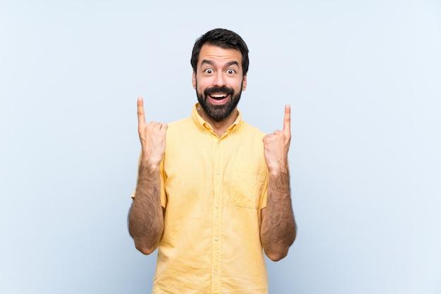 Jovem com barba sobre parede azul isolada apontando uma ótima idéia
