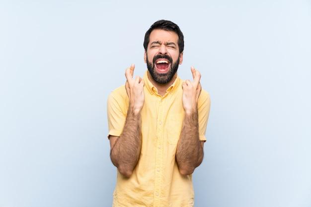 Jovem com barba sobre parede azul isolada com dedos cruzando