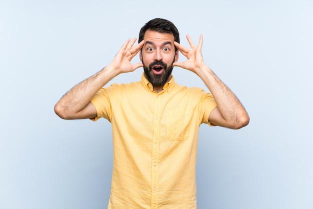 Jovem com barba sobre parede azul isolada com expressão de surpresa