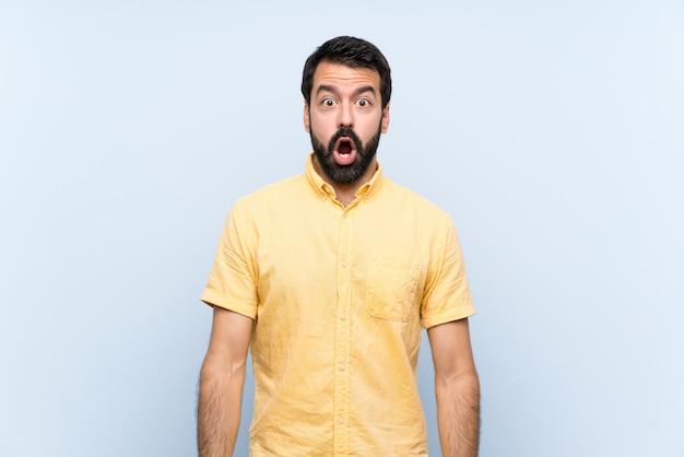 Jovem com barba sobre parede azul isolada com expressão facial de surpresa