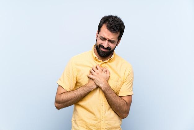 Jovem com barba sobre parede azul isolada, com uma dor no coração