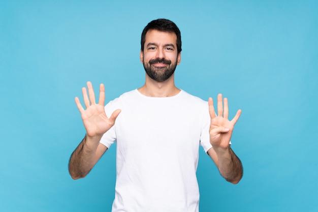 Jovem com barba sobre parede azul isolada, contando nove com os dedos