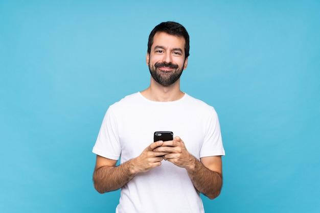 Jovem com barba sobre parede azul isolada, enviando uma mensagem com o celular