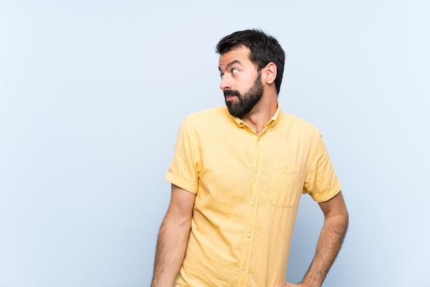 Jovem com barba sobre parede azul isolada, fazendo dúvidas gesto olhando de lado