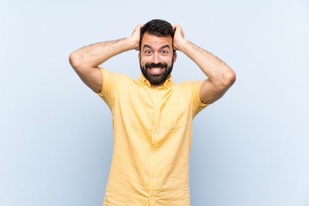 Jovem com barba sobre parede azul isolada frustrada e leva as mãos na cabeça