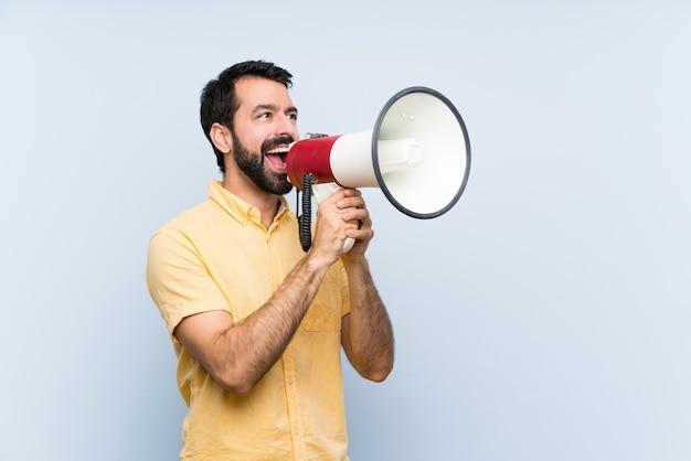 Jovem com barba sobre parede azul isolada, gritando através de um megafone