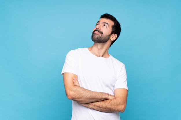 Jovem com barba sobre parede azul isolada, olhando para cima enquanto sorrindo
