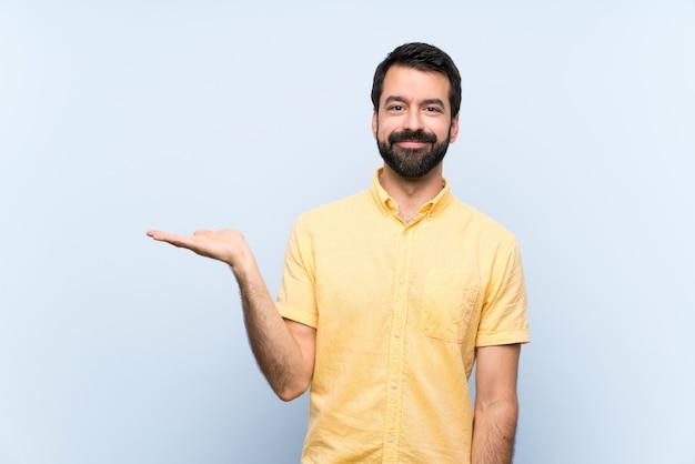 Jovem com barba sobre parede azul isolada, segurando copyspace imaginário na palma da mão para inserir um anúncio