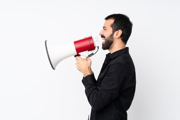 Jovem com barba sobre parede branca isolada, gritando através de um megafone