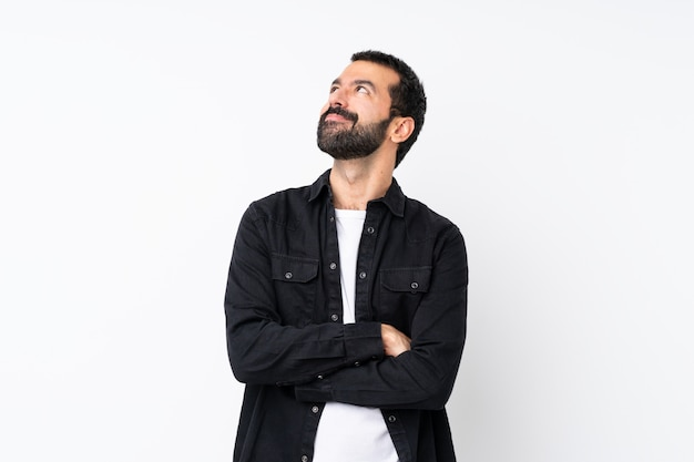 Jovem com barba sobre parede branca isolada, olhando para cima enquanto sorrindo