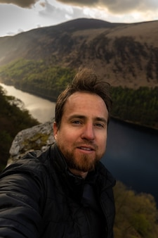 Jovem com barba tirando uma selfie na montanha com um lago ao fundo na irlanda de wicklow