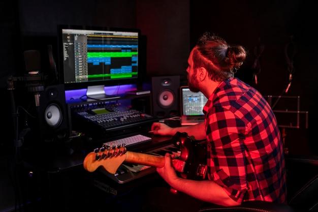 Jovem com barba tocando violão no estúdio estéreo no rádio para gravar sua nova música