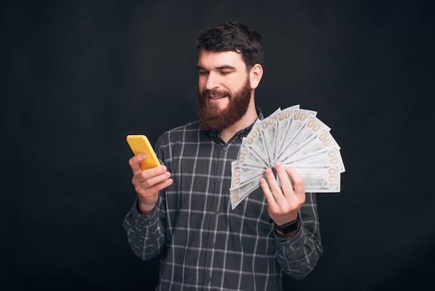 Jovem com barba usando smartphone e segurando o dinheiro