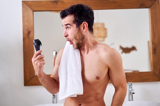 Jovem com barbeador elétrico na mão e uma toalha no ombro em pé perto do espelho na banheira pela manhã