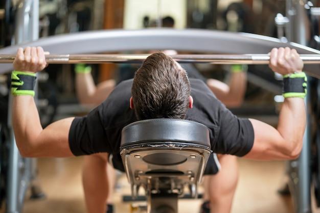 Jovem com barra flexionando os músculos e fazendo supino no ginásio