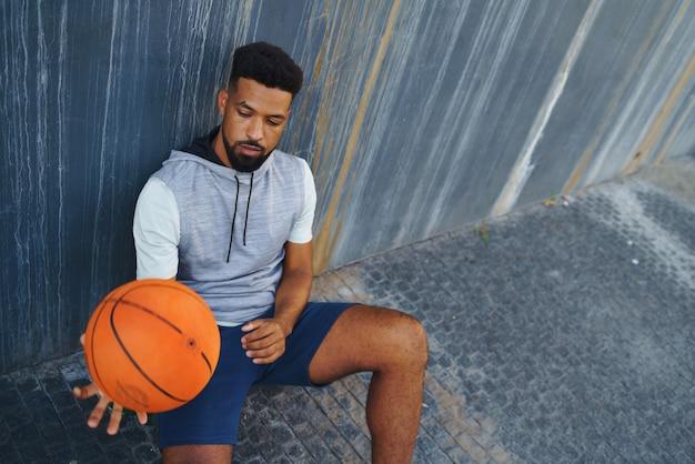 Jovem com basquete fazendo exercício ao ar livre na cidade, sentado e descansando.