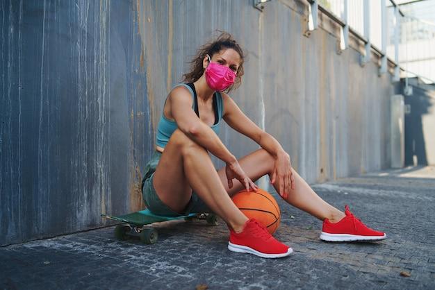 Jovem com basquete sentado e olhando para a câmera ao ar livre na cidade, o conceito de coronavírus.