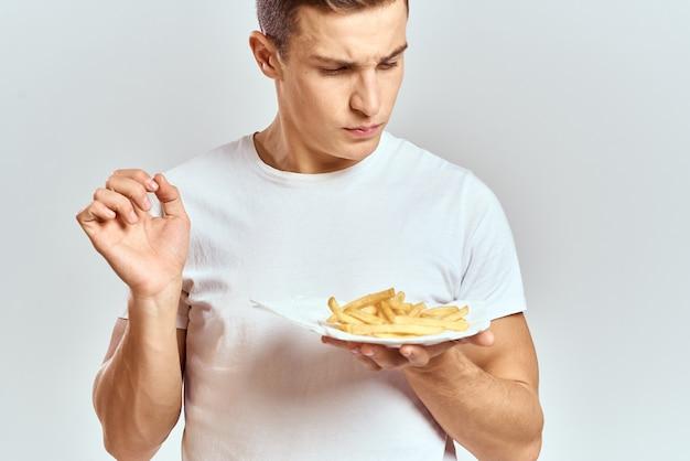 Jovem com batatas fritas em uma caixa e uma camiseta branca em uma parede de luz