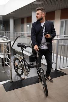 Jovem com bicicleta dobrável na escada rolante