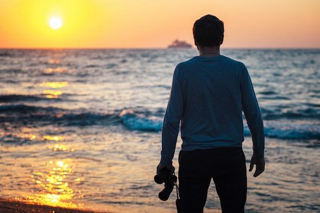 Jovem com binóculos nas mãos, olhando para o mar durante o pôr do sol