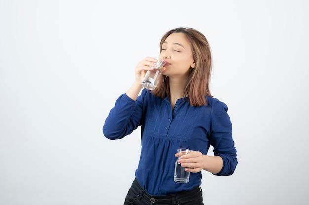 Jovem com blusa azul bebendo um copo de água na parede branca.