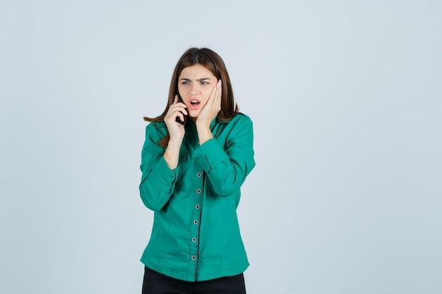 Jovem com blusa verde, calça preta, falando ao telefone, segurando a mão na bochecha e parecendo chocada, vista frontal.