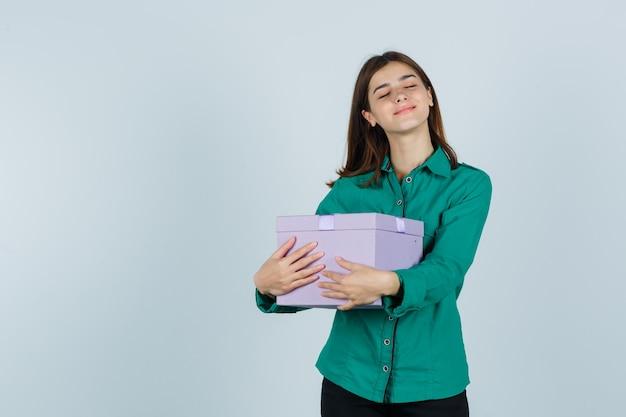 Jovem com blusa verde, calça preta segurando a caixa de presente contra o peito e parecendo feliz, vista frontal.
