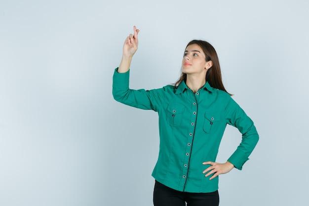 Jovem com blusa verde, calça preta segurando os dedos cruzados, colocando a mão no quadril e parecendo feliz, vista frontal.