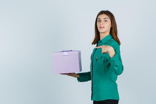 Jovem com blusa verde, calça preta segurando uma caixa de presente, apontando para ela e olhando alegre, vista frontal.