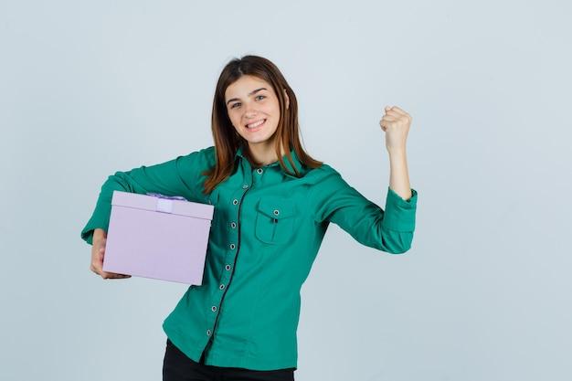 Jovem com blusa verde, calça preta segurando uma caixa de presente, mostrando o gesto do vencedor e parecendo com sorte, vista frontal.