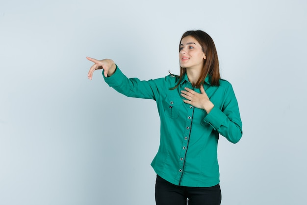Jovem com blusa verde, calça preta, segurando uma mão sobre o peito, apontando com o dedo indicador e olhando feliz, vista frontal.
