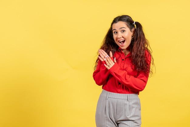 Jovem com blusa vermelha batendo palmas alegremente em amarelo