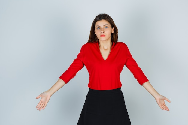 Jovem com blusa vermelha, saia esticando os braços para o lado e parecendo indefesa