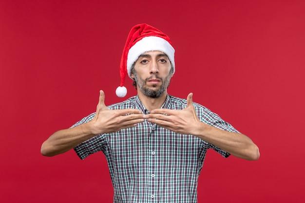 Jovem com boné de ano novo na parede vermelha homem de feriado vermelho