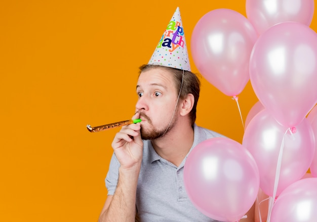 Jovem com boné de férias comemorando festa de aniversário segurando um monte de balões, feliz e positivo sobre laranja