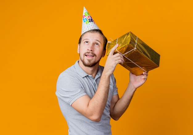 Jovem com boné de férias comemorando festa de aniversário segurando uma caixa de presente perto da orelha com expressão pensativa em pé sobre a parede laranja