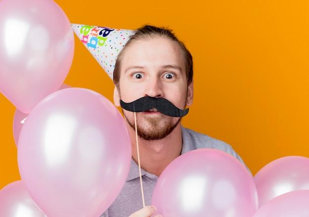 Jovem com boné de férias segurando um palito de festa com bigode surpreso com o conceito de festa de aniversário em pé com balões de ar sobre a parede laranja
