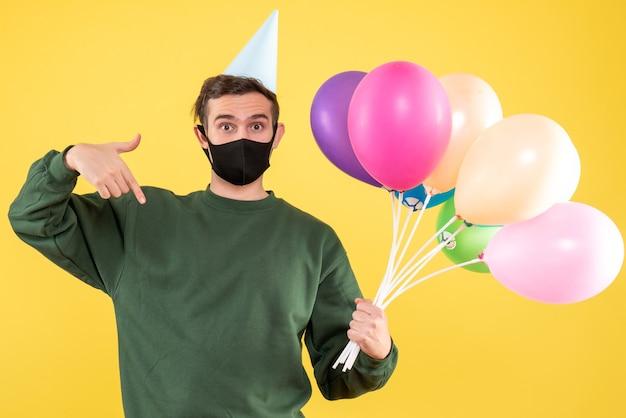 Jovem com boné de festa e balões coloridos apontando com o dedo para baixo em amarelo