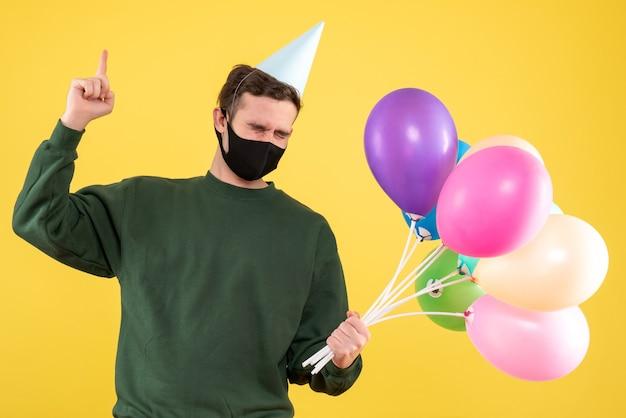 Jovem com boné de festa e balões coloridos apontando com o dedo para cima em amarelo