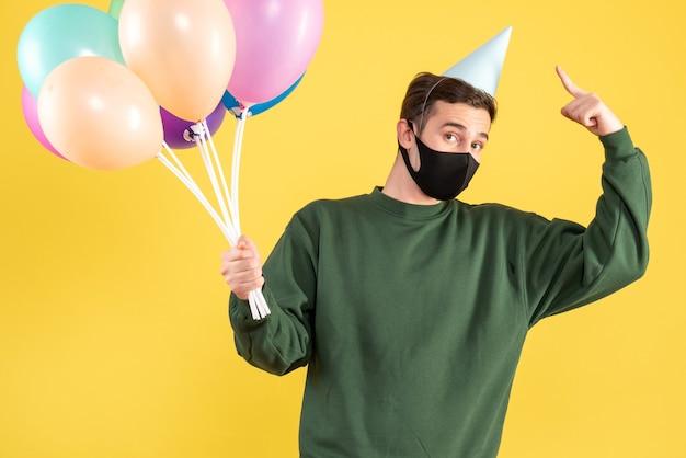 Jovem com boné de festa e balões coloridos apontando para o boné em amarelo