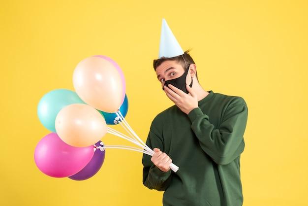 Jovem com boné de festa e balões coloridos colocando a mão no rosto em amarelo