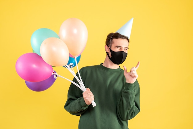 Jovem com boné de festa e balões coloridos em pé sobre amarelo
