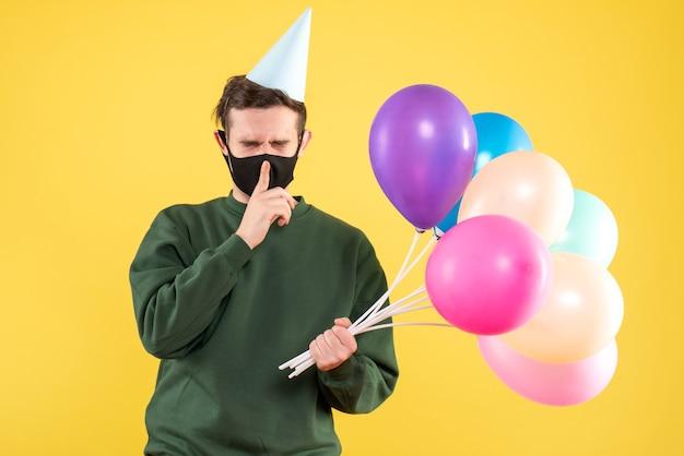 Jovem com boné de festa e balões coloridos fazendo shh sinal de pé em amarelo