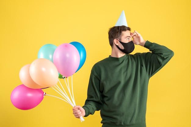 Jovem com boné de festa e balões coloridos olhando de frente para algo amarelo