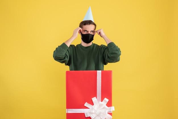 Jovem com boné de festa e máscara preta em frente a uma grande caixa de presente em amarelo