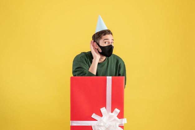 Jovem com boné de festa ouvindo algo atrás de uma grande caixa de presente em fundo amarelo com vista frontal