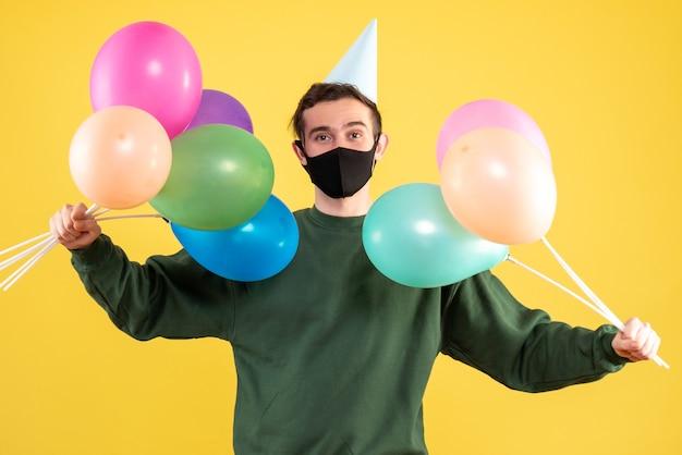 Jovem com boné de festa segurando balões com as duas mãos em frente ao fundo amarelo