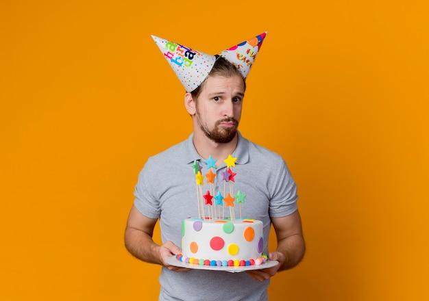 Jovem com bonés de férias confuso segurando um bolo de aniversário conceito de festa em pé sobre uma parede laranja